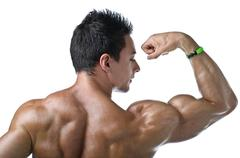 Muscular young bodybuilder's back. looking at bicep Stock Photos