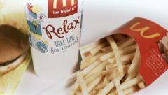 Drink, burger and fries rotating on white - stock footage