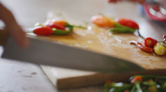 Chili peppers cut at chopping board - close up Stock Footage
