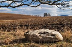 Big white stone next to the undulating plowed field in early spring Stock Photos