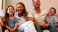 Happy young family laughing on couch Stock Footage