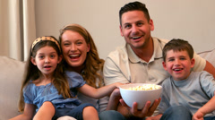 Happy family watching television eating popcorn Stock Footage