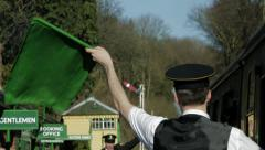 Guard waving green flag and train moving off Stock Footage