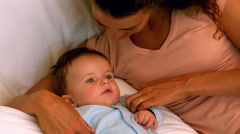Mother cuddling her baby boy on bed Stock Footage