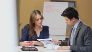 Stock Video Footage of Business meeting, man and woman briefing reading charts solution