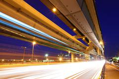 elevated freeway with traffic trail - stock photo
