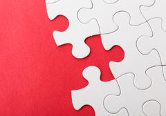 Incompleted white puzzle with red background Stock Photos