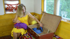 girl with dress sitting on bed on knees clothe put into suitcase - stock footage