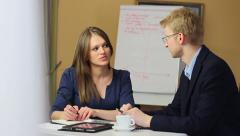 Young attractive female office worker with man on work meeting Stock Footage