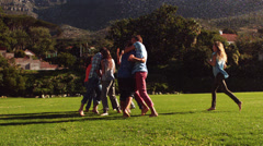 Students messing around in the sprinklers on the grass Stock Footage