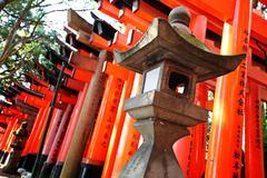 Stone lantern with torii Stock Photos