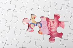 chinese yuan and puzzle piece - stock photo