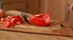 Woman hands slicing sweet Red Bell Pepper on a wooden cutting board Stock Footage