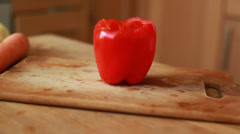 Woman hands slicing sweet Red Bell Pepper on a wooden cutting board - stock footage