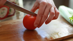 Woman hands slicing red tomato in kitchen Stock Footage