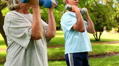 Retired couple lifting weights outside Stock Footage