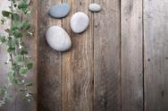 Stock Photo of leaves and stones over wooden background.