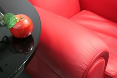 Red apple and a red easy chair Stock Photos