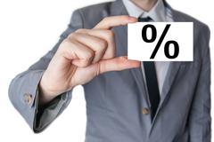 Percent sign for interest. businessman in suit with a black tie showing or ho Stock Photos