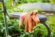Stock Photo of orange plastic gloves on arm chair in the park