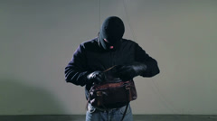 Masked criminal looking in  a leather bag wearing gloves Stock Footage
