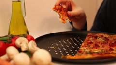 Hungry young man eating tasty pizza, Italian cuisine, fresh vegetables Stock Footage