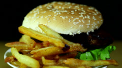 Hamburger with fried potato in rotation close up Stock Footage
