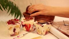 Hand putting fresh fruits in a basket, cereals, yogurt, healthy breakfast Stock Footage