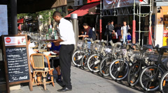 Waiter serving customers at outdoor cafe in Paris Stock Footage