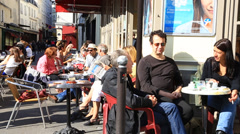 People at the sunlit cafe terrace in Paris Stock Footage