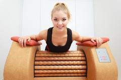 girl in sportwear using relax massage equipment healthy spa salon - stock photo
