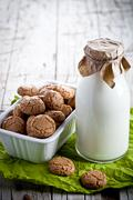 Meringue almond cookies in a bowl and bottle of milk Stock Photos