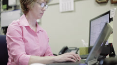 Mature female network administrator working on laptop in office Stock Footage