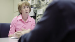 Woman network admin using tablet pc discusses with coworker Stock Footage