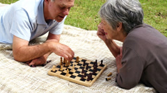 Senior couple relaxing in the park lying on a blanket playing chess Stock Footage