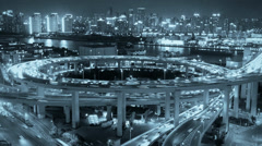 Night heavy traffic on highway interchange,Brightly lit cityscape,busy shipping Stock Footage