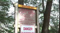Cliff area warning in forest tilt shot Stock Footage
