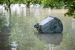 floating dumpster in flood - stock photo