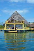 Tropical bungalow over water with thatched roof Stock Photos