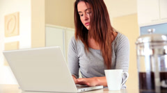 Pretty brunette sitting using laptop and drinking coffee Stock Footage
