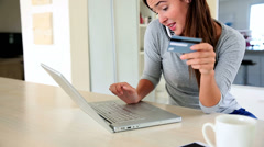 Pretty brunette using laptop to shop online while talking on phone Stock Footage