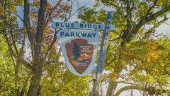 Motorcycles Passing Nostalgic Blue Ridge Parkway Sign near Asheville, NC Stock Footage