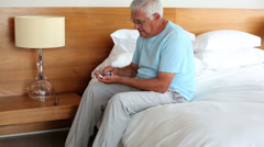 Senior man sitting on bed taking his medicine Stock Footage