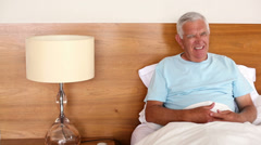 Senior man sitting in bed having a heart attack Stock Footage