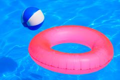 colorful inflatable ball and round tube floating in swimming pool - stock photo