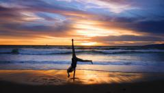 Girl doing cartwheel on a beach at scenic sunset. Slow motion. Stock Footage