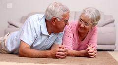 Senior couple lying on floor chatting - stock footage