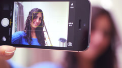 Female taking self portrait with smart phone - stock footage