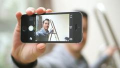 Young man self photographing with smart phone Stock Footage