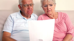 Worried senior couple reading a document Stock Footage